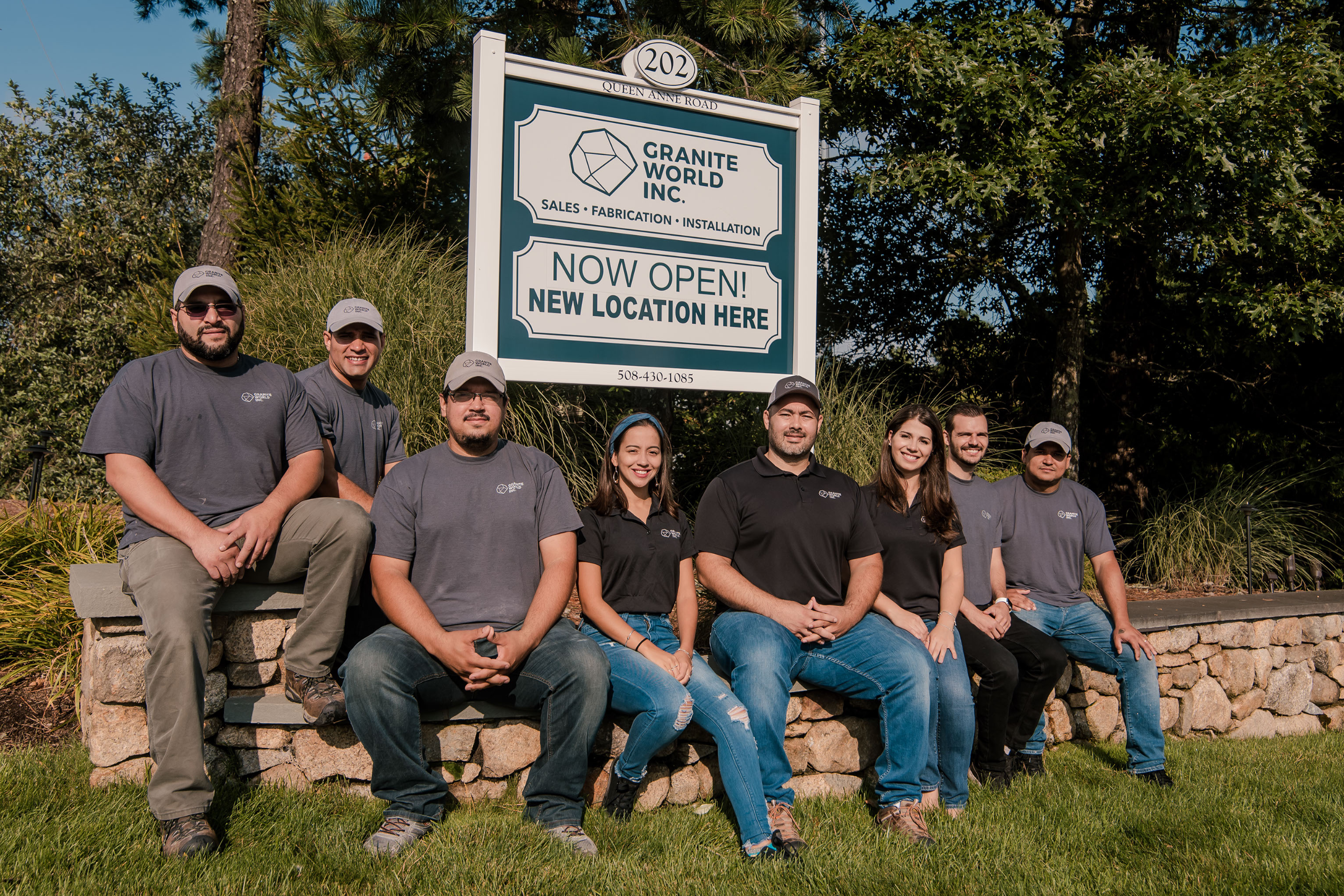 Our Team- Employees sitting next to warehouse sign - Granite World - Harwich, Massachusetts - Cape Cod